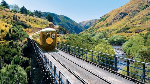 Train cutting through the mountains near a river in Otago