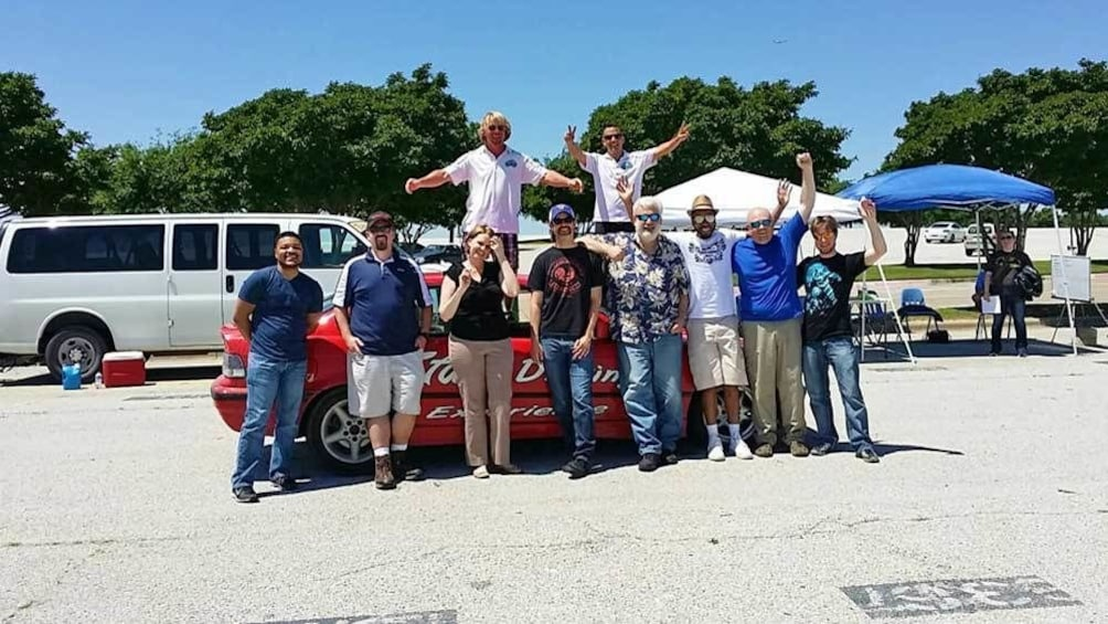 Show item 3 of 5. group of participants in front of a stunt car in Ontario