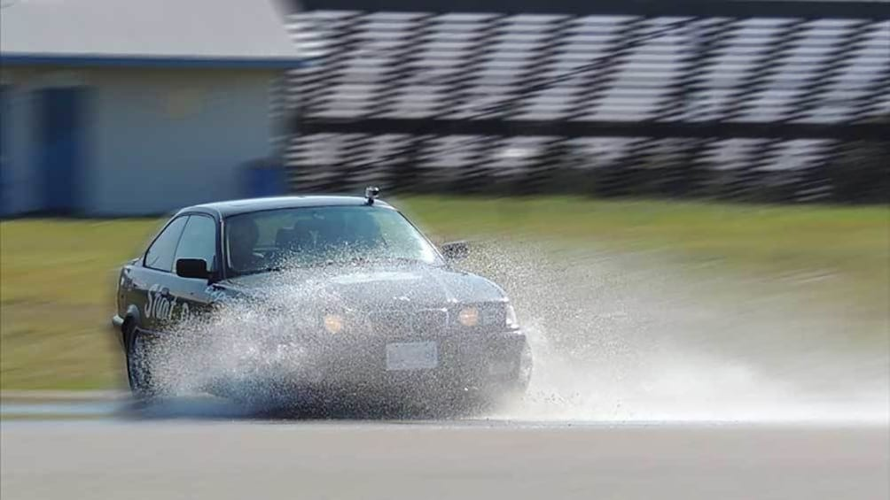 Show item 1 of 5. stunt car performing a drift on the wet track in Ontario