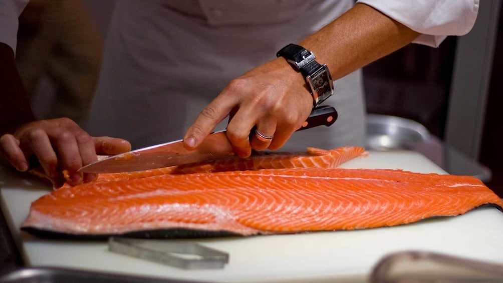 chef cutting fish on a block in Australia