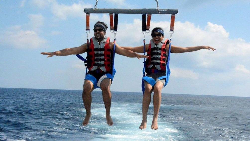 Charger l'élément 2 sur 5. Parasailing couple low over the water in Santorini