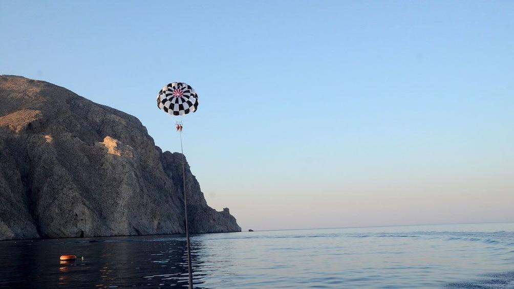 Charger l'élément 4 sur 5. Parasailer high in the air near coastal cliffs in Santorini
