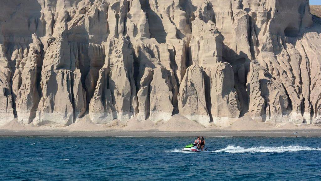 Jet skiing couple near rock formations along the coast of Santorini