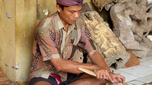 Local doing wood carvings in Bali