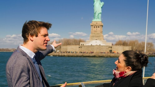 Two people next to the Statue of Liberty on a boat