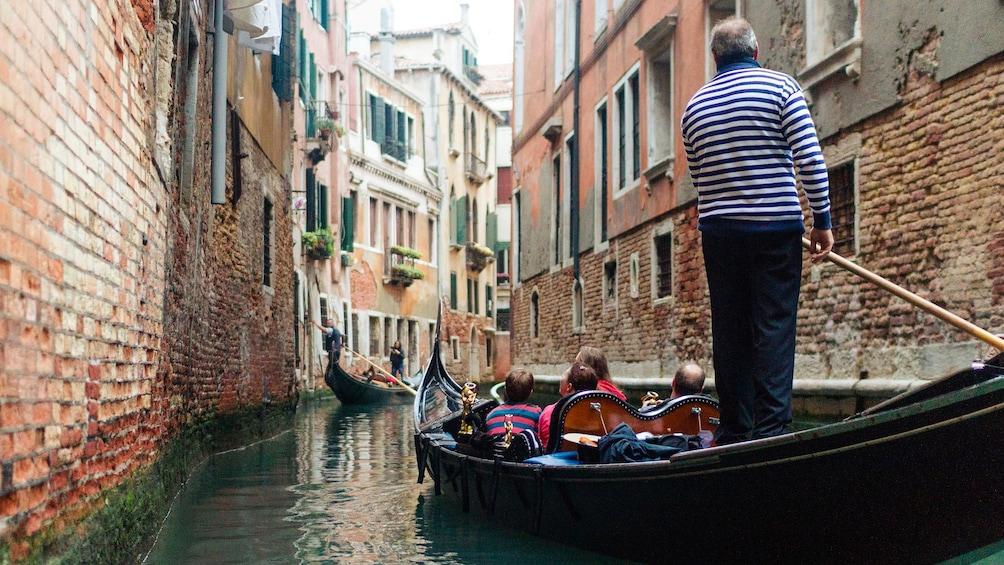 Man takes Gondola through canal in Venice