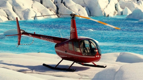 Helicopter landed on a glacier near a lake in Anchorage