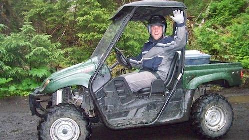 Man in ATV waving at camera.