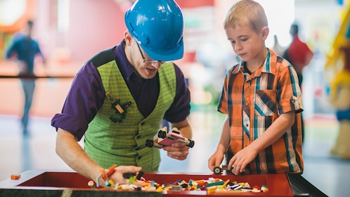 Legoland employee and child constructing toy together.