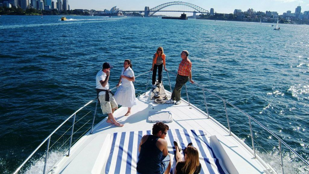 People stand on the bow of a yacht