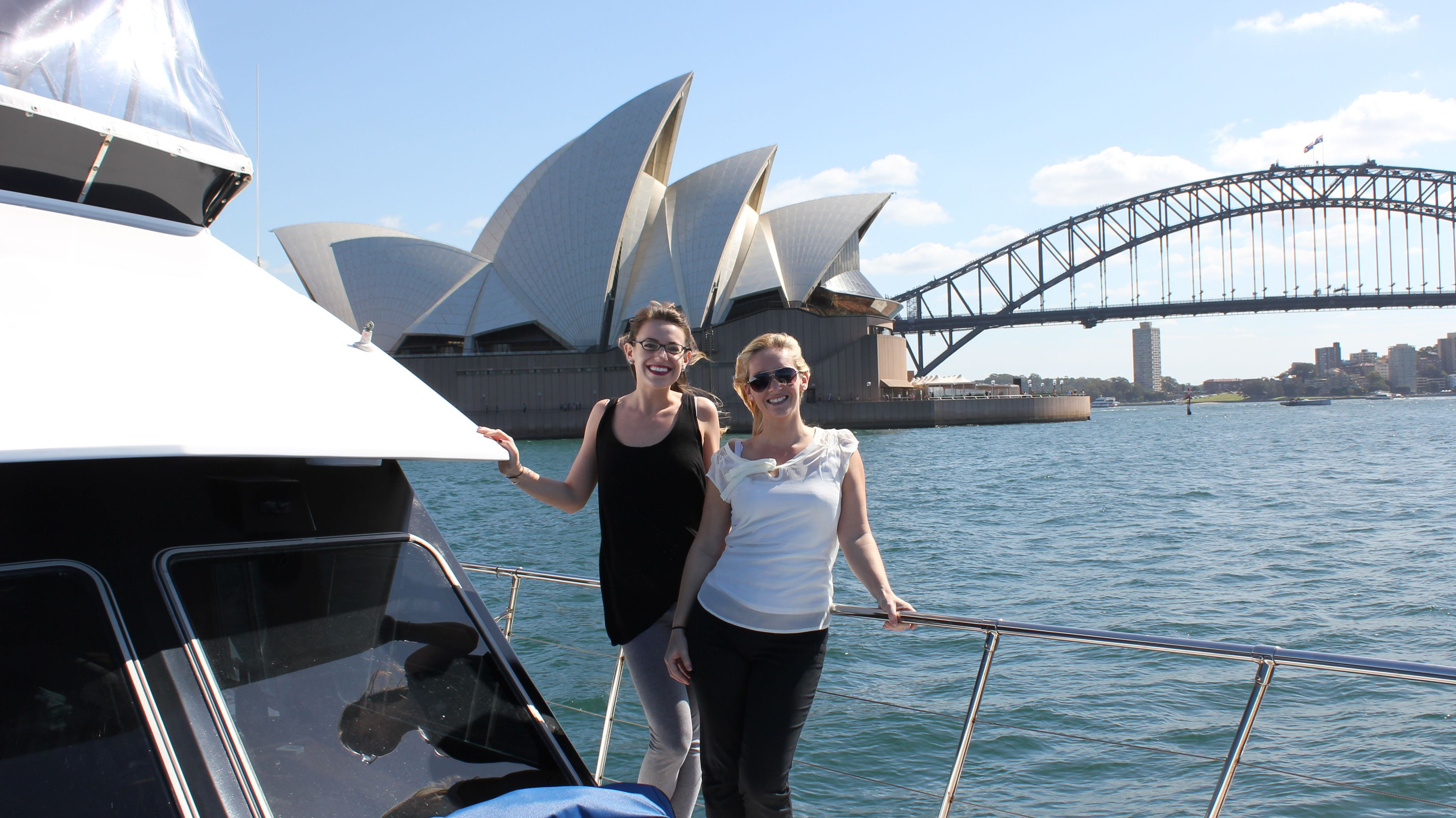 Two women pose on a yacht in Sydney harbor