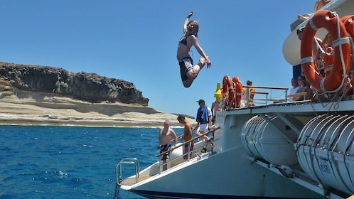 woman diving from stern of boat