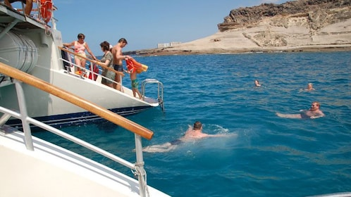 people swimming around boat