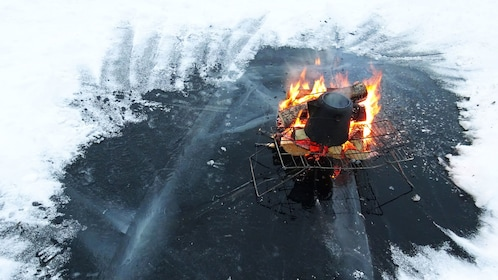 camp fire built on icy lake