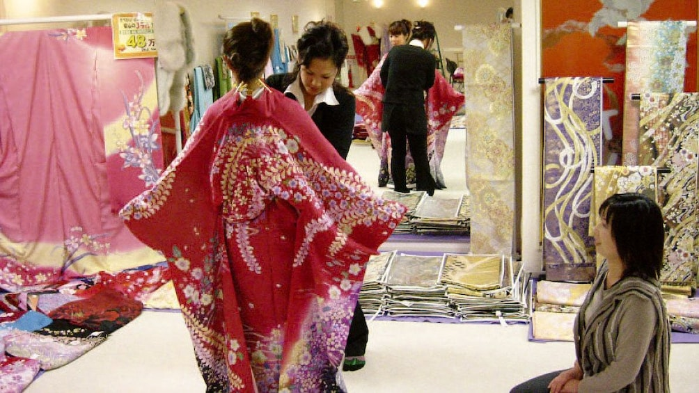 Show item 2 of 5. Woman being fitted for a kimono