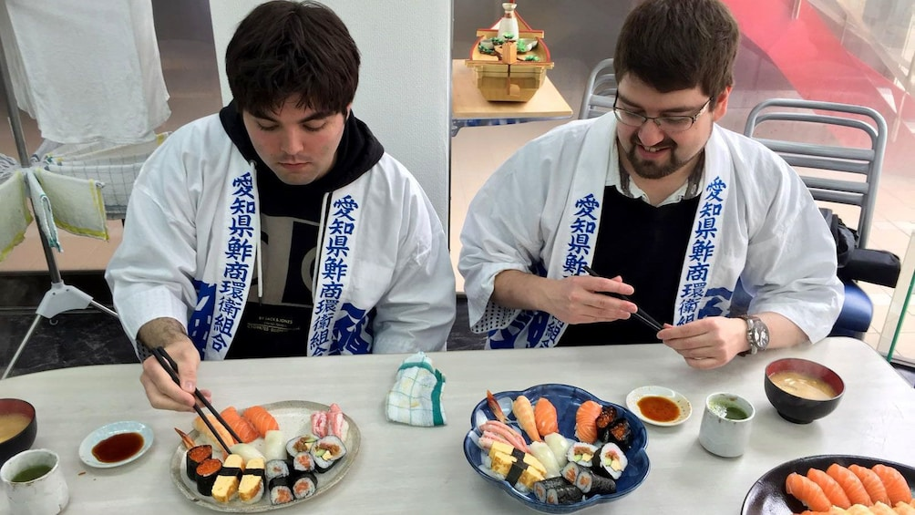Show item 3 of 5. Couple of men eating the sushi they prepared