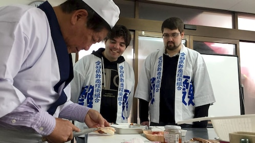 Men watching sushi chef prepare food in a kitchen in Nagoya