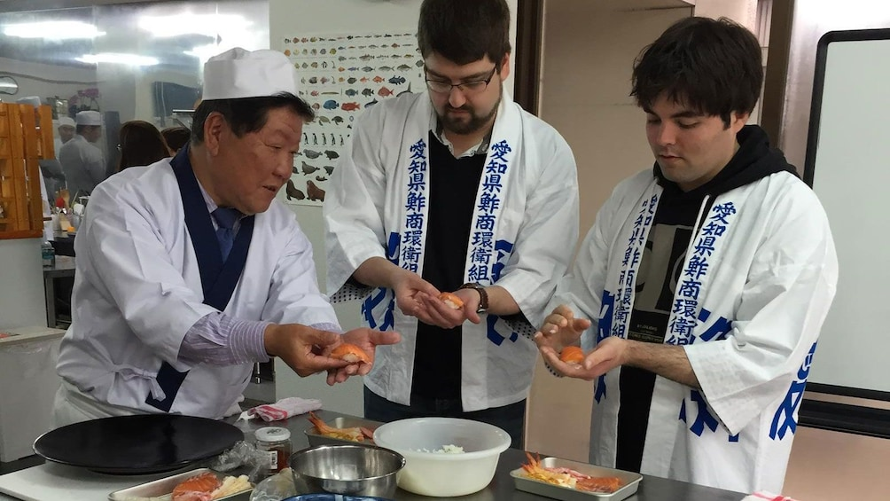 Show item 1 of 5. Sushi chef giving a class instructions in the kitchen