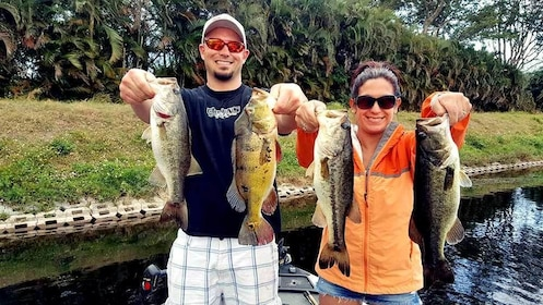 couple holding up fishes in Boca Raton