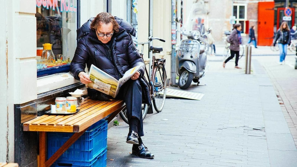 Foto 2 van 10. man reading outside a cafe in Amsterdam