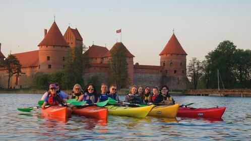 Several tourists on colorful kayaks near Trakai.
