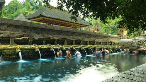 People bathing in a hot spring in Bali