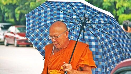 Monk in orange robe holding umbrella in Chiang Mai