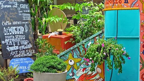 Close up of shop sign surrounded by several plants.