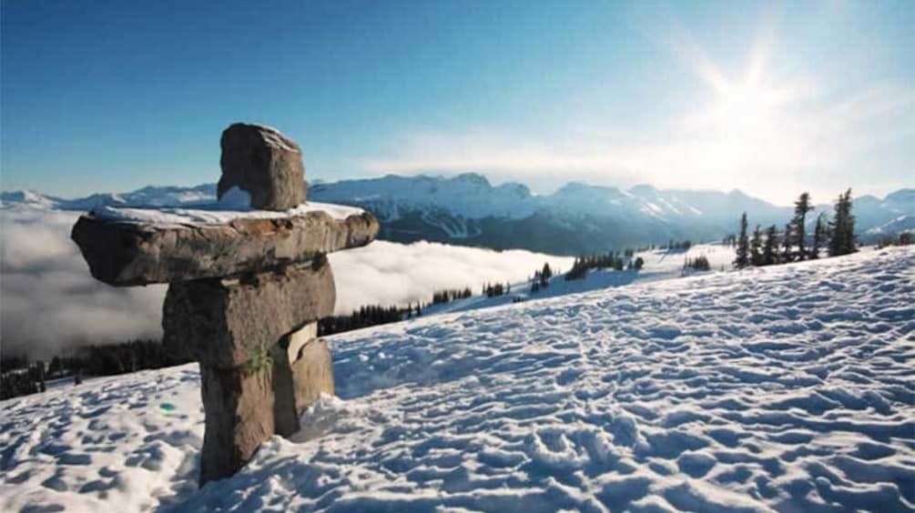 Show item 1 of 9. Inukshuk rock sculpture on a snowy hill in Whistler