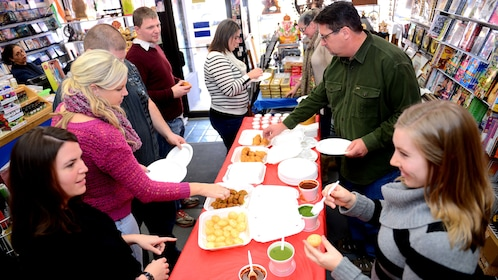 People eat Indian food in a shop