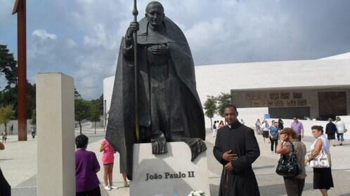 Priest next to image of Joao Paulo II