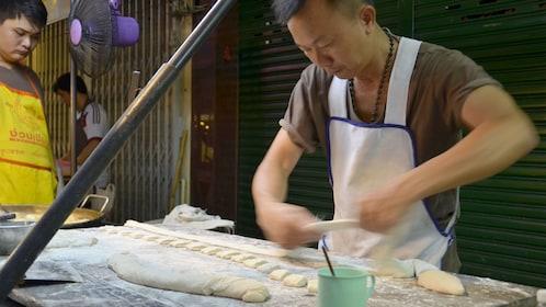Man cutting dough seen on the Chinatown food tour in Bangkok