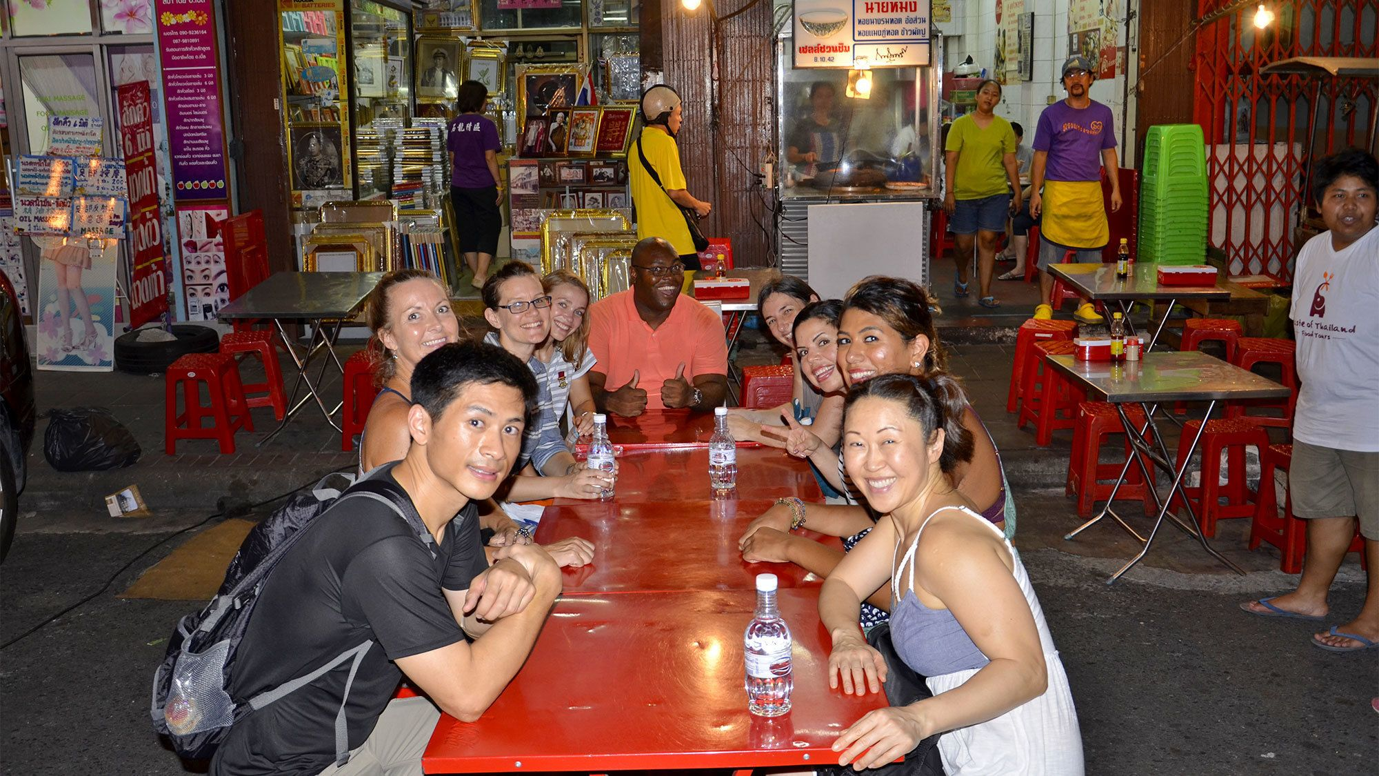 Group getting ready to eat at an outside table at night in Bangkok