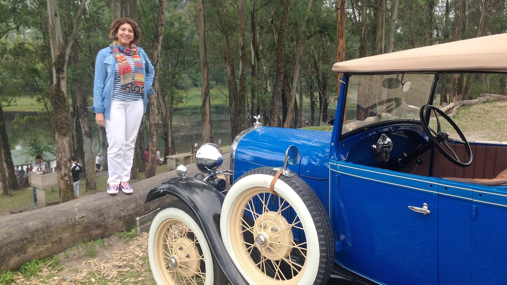 Show item 3 of 5. Woman poses next to a blue car on the Antique Tour in Argentina Northwest, Argentina