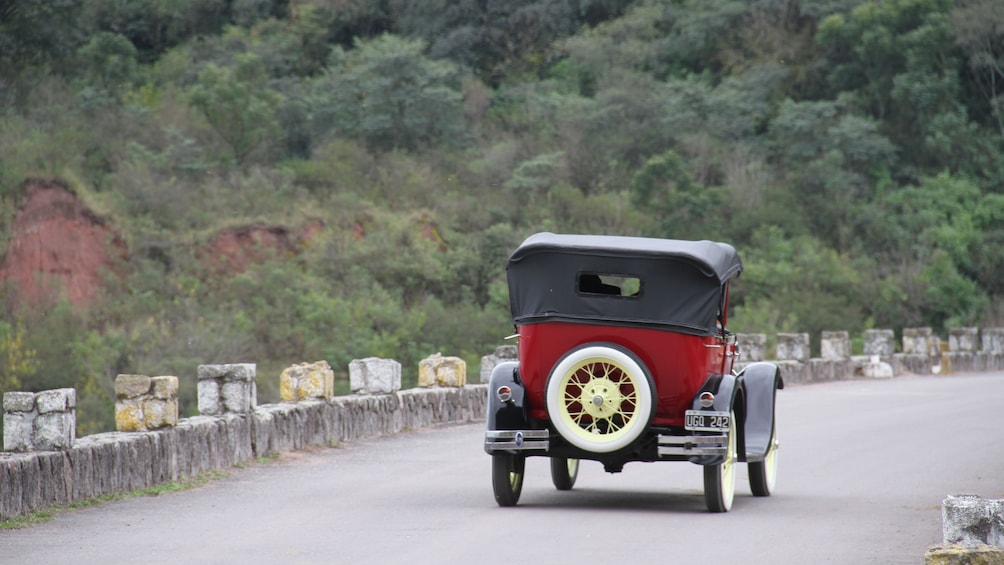 Show item 3 of 5. antique red car from behind on the road