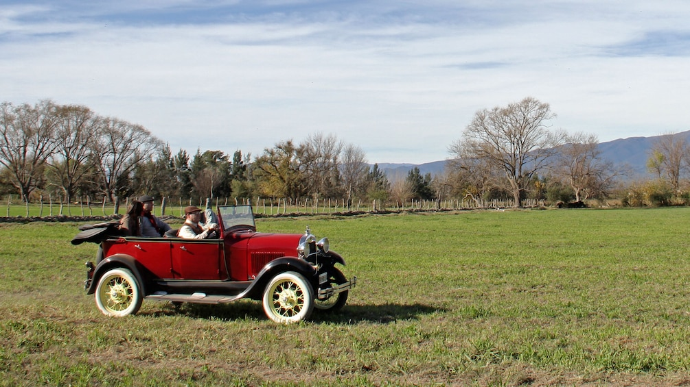 Show item 1 of 5. antique red car in field