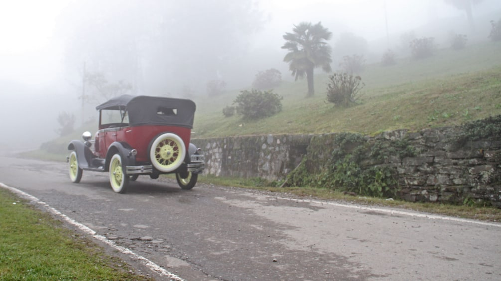 Show item 4 of 5. antique car on misty road