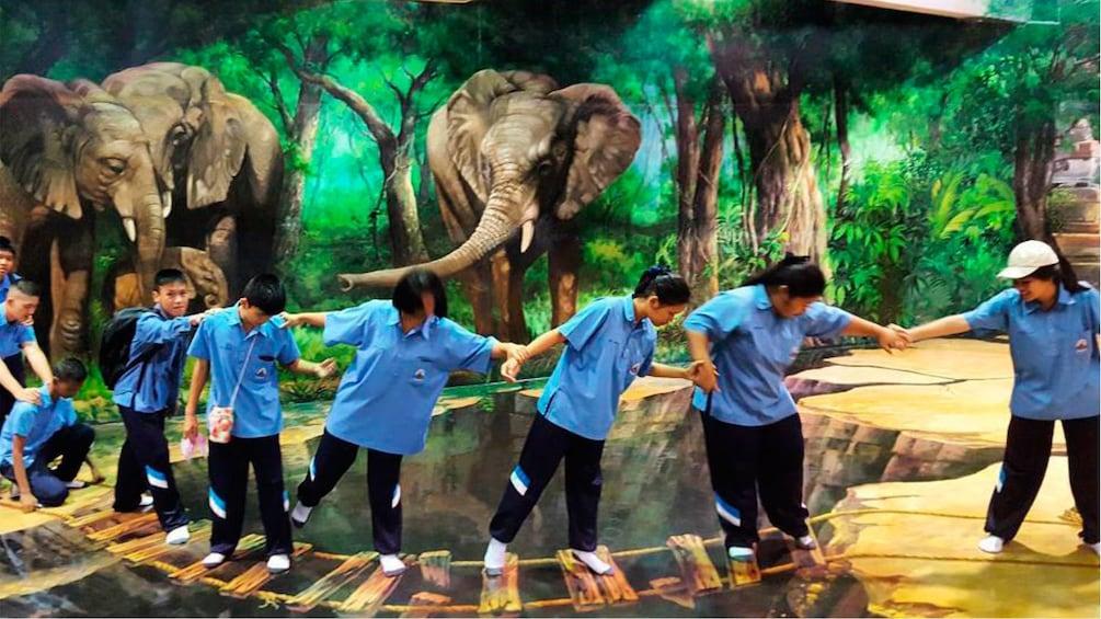 正在顯示第 3 張相片,共 4 張。 Group pretending to cross a fake bridge in an optical illusion exhibit in Pattaya