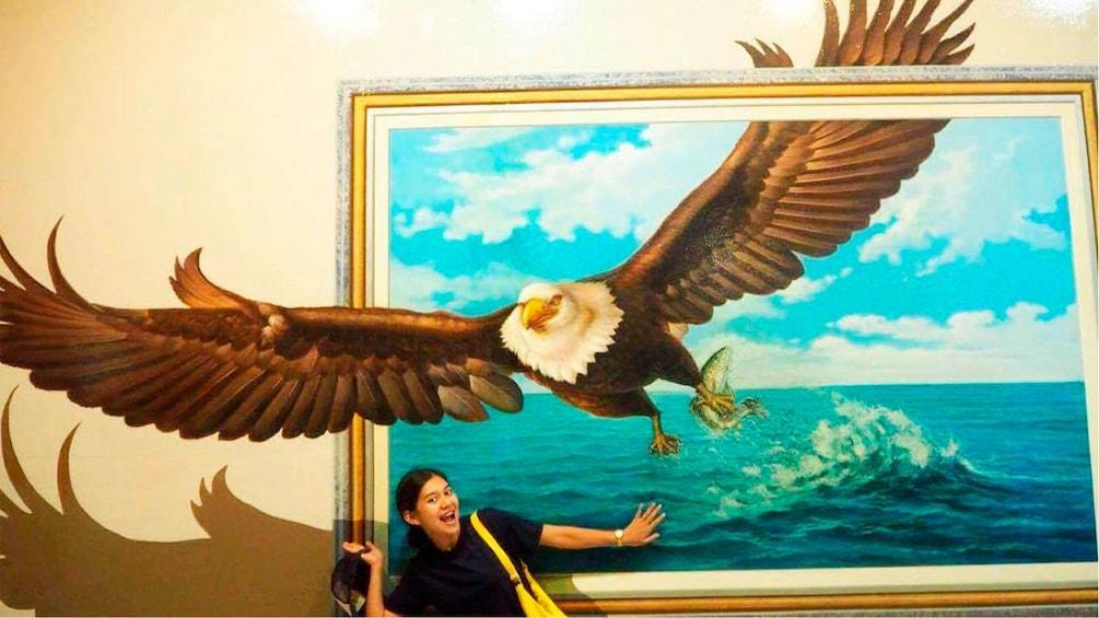正在顯示第 2 張相片,共 4 張。 Girl posing with optical illusion painting of an eagle in Pattaya