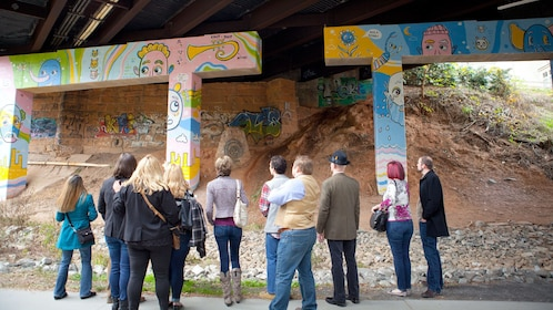 Tour group under a bridge looking at graffiti in Atlanta