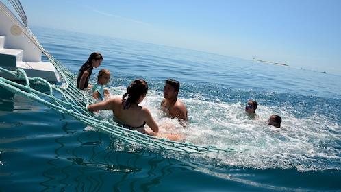 Group swimming alongside a catamaran in Australia