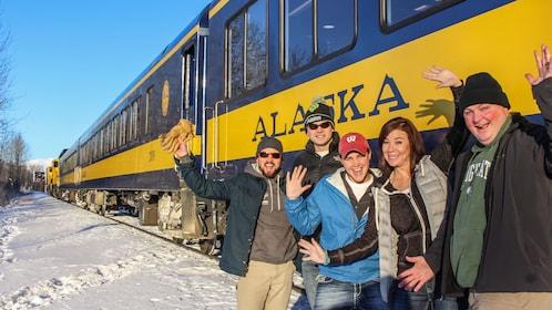 People pose outside a train