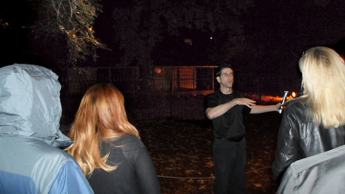 Tour guide and group at haunted cabin in Fort Worth