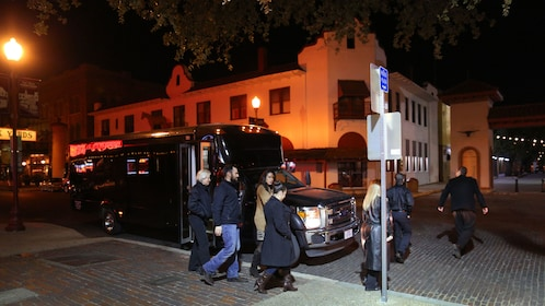Passengers boarding ghost tour bus at night in Fort Worth