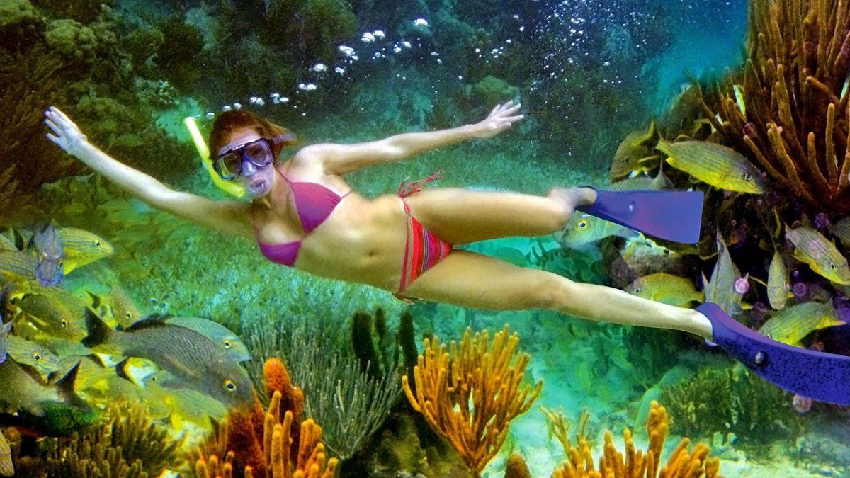 snorkeler waving from underwater in Cancun