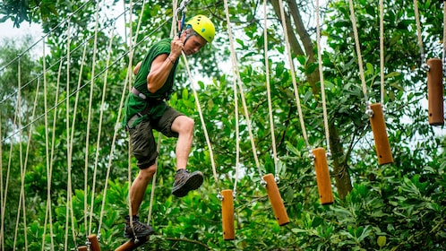 man walking through rope steps in Vietnam