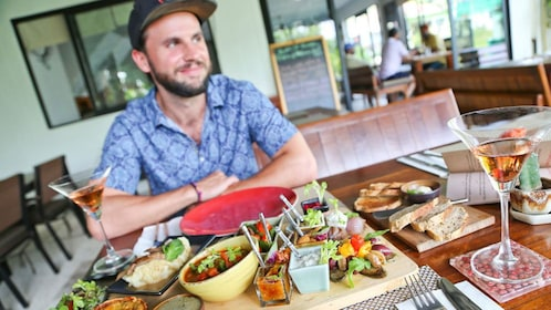Man sits at table with food and drinks