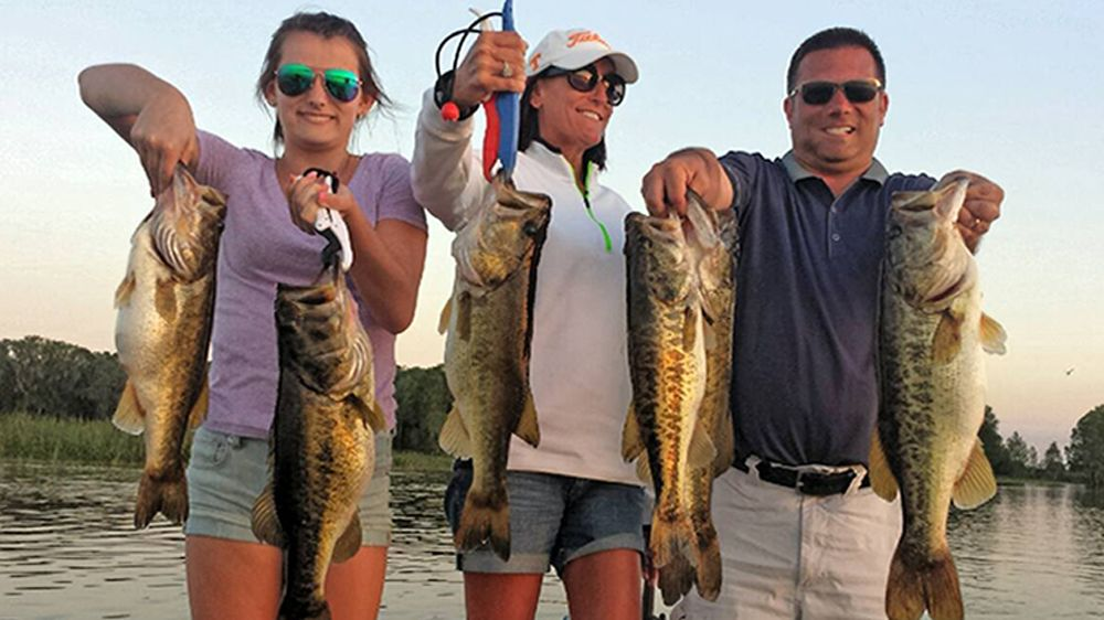 Three people hold up Bass they caught while fishing in Kissimmee