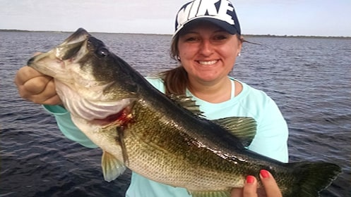 Woman holds up a Bass she caught in Kissimmee
