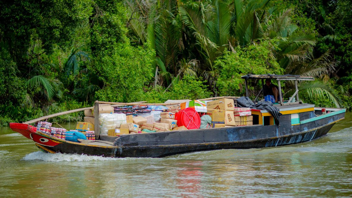 Boat hauling goods down river in Ho Chi Minh City, Vietnam